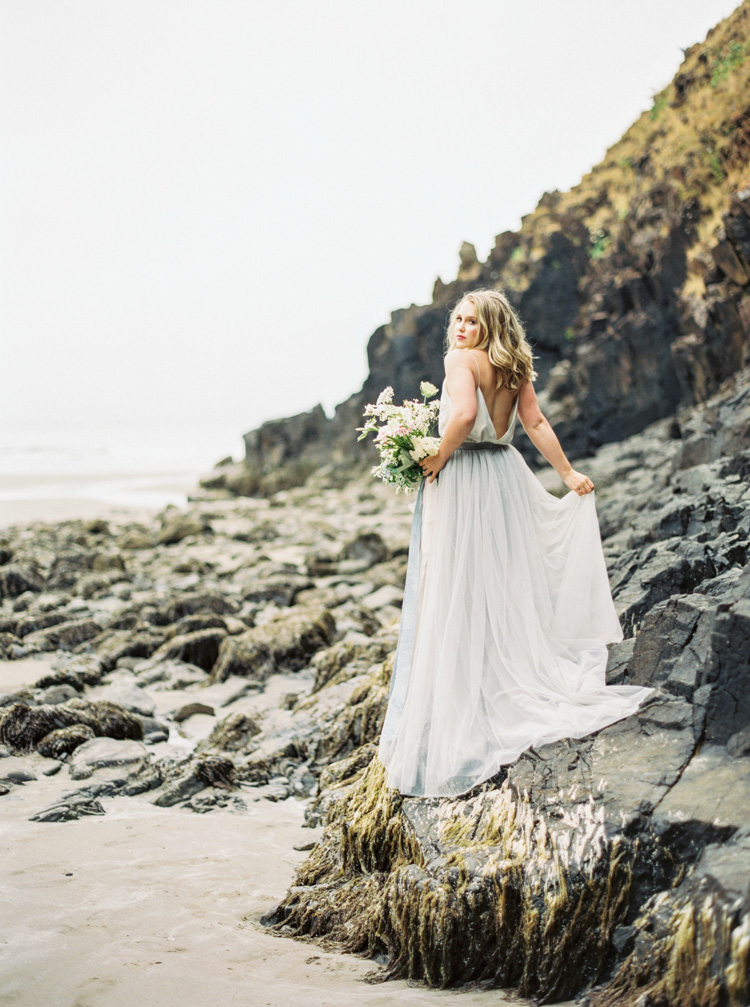 Bride on black rocks in Cannon Beach Oregon by Shannon Skloss