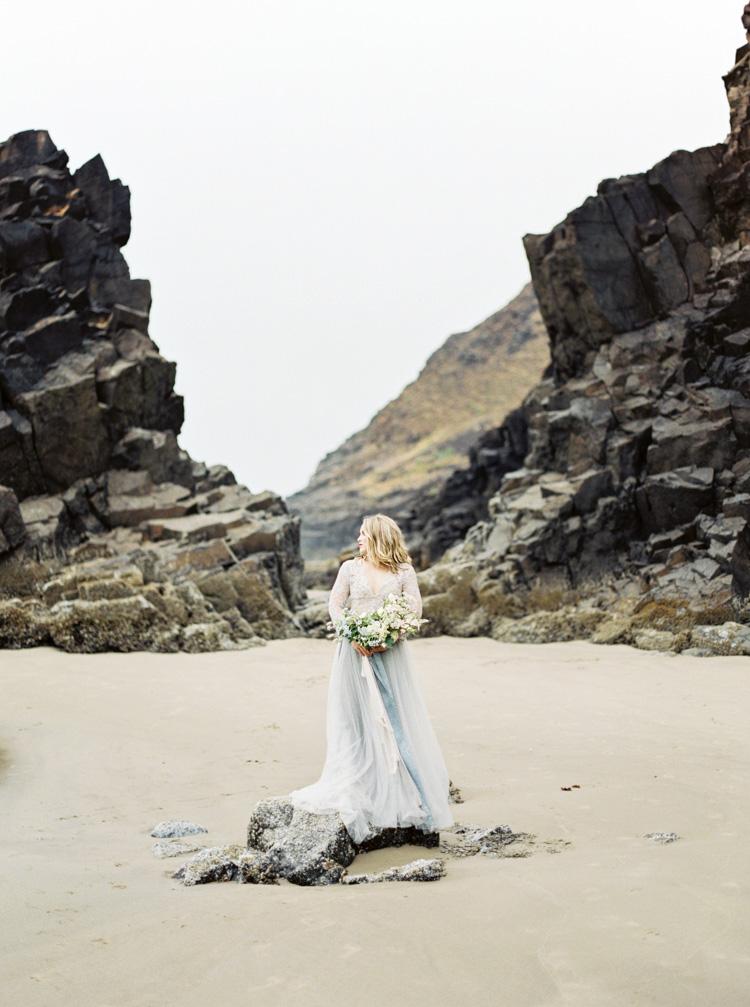 Bride on black rocks in Cannon Beach Oregon by Shannon Skloss